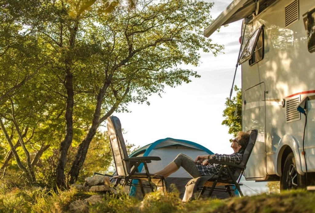 A retired woman enjoying RV living, camping outdoors in a beauty spot.