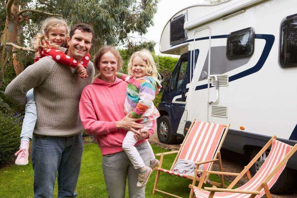Family of four in front of an RV Motorhome