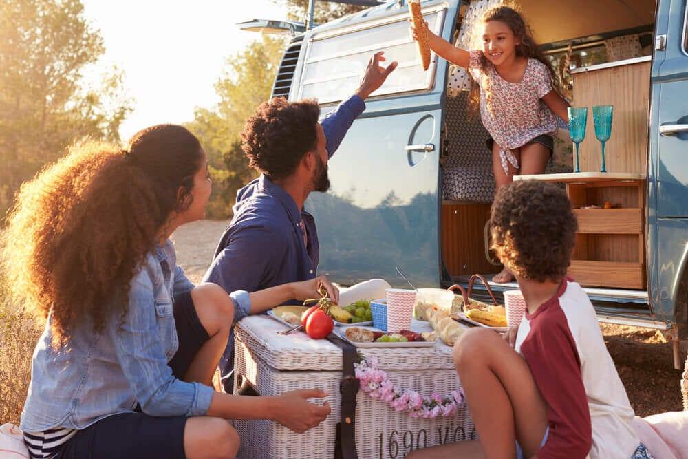 Family of 4 near camper van enjoying eating outdoors