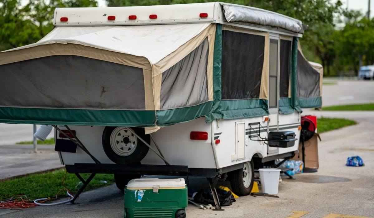 Pop-up rv camper at a camp ground with a cooler and barbecue on site